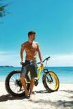 Человек с велосипедом песка на пляже наслаждаясь каникулами перемещения лета Стоковые Фотографии RF