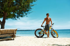 Человек с велосипедом песка на пляже наслаждаясь каникулами перемещения лета Стоковое Изображение