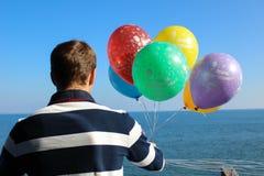 Человек с воздушными шарами на его дне рождения наблюдая от балкона t стоковые изображения rf