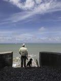 Человек с горизонтом собаки наблюдая моря от малой пристани Нормы стоковые фото