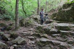 Человек с горным велосипедом на каменном пути в древесинах Стоковое Изображение RF