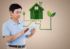Человек с графиком таблетки и зеленого дома против cream предпосылки Стоковые Изображения RF