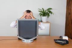 Человек с его компьютером на месте дела Стоковые Фото