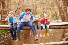 Человек с детьми на мосте в центре мероприятий на свежем воздухе Стоковые Изображения