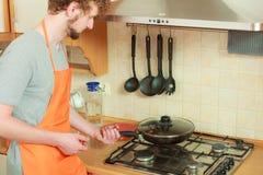 Человек с жарить лоток фрая в кухне Стоковые Фотографии RF