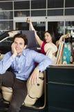 Человек с женщиной Shopaholic в автомобиле с откидным верхом Стоковое Фото