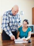 Человек с задумчивой зрелой женой заполняет внутри вопросник Стоковая Фотография RF