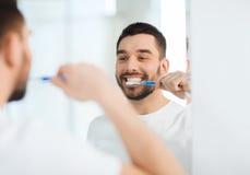 Человек с зубами чистки зубной щетки на ванной комнате Стоковое фото RF