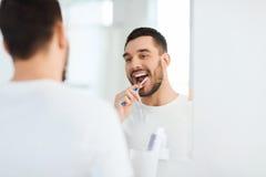 Человек с зубами чистки зубной щетки на ванной комнате Стоковые Фотографии RF