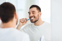 Человек с зубами чистки зубной щетки на ванной комнате Стоковые Фото