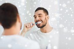 Человек с зубами чистки зубной щетки на ванной комнате Стоковое Изображение RF