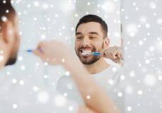 Человек с зубами чистки зубной щетки на ванной комнате Стоковая Фотография RF