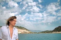 Человек с длинными волосами на предпосылке моря, островов и облаков стоковое изображение