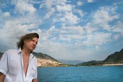 Человек с длинными волосами на предпосылке моря стоковое изображение rf