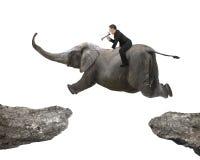 Человек с использованием слона катания диктора летая над 2 скалами Стоковые Изображения RF