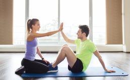 Человек с личным тренером делать сидит поднимает в спортзале стоковые фото