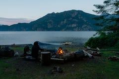 Человек с каяком около лагерного костера на пляже в вечере Стоковая Фотография RF