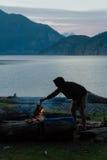 Человек с каяком около лагерного костера на пляже в вечере Стоковая Фотография