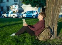 Человек с компьтер-книжкой в парке Стоковая Фотография