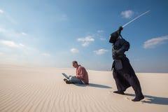 Человек с компьтер-книжкой над им самурай с шпагой, как deadl Стоковые Фото