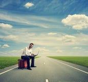 Человек с компьтер-книжкой на скоростной дороге стоковые фото