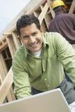 Человек с компьтер-книжкой на строительной площадке Стоковое Изображение