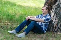 Человек с компьтер-книжкой сидит на лужайке около большой старой сосны Стоковое фото RF