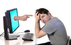 Человек с компьютером обвиняя палец cyberbullying стоковые фото