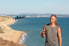 Человек с контролируемым трутнем на пляже Стоковое Фото