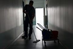 Человек с коридором офиса чистки веника Стоковые Фото