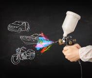 Человек с краской для пульверизатора airbrush с автомобилем, шлюпка и мотоцикл рисуют Стоковая Фотография