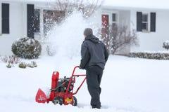 Человек с красной воздуходувкой снега стоковые изображения