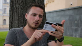 Человек с кредитной карточкой во время покупок через интернет используя умный телефон в парке сидя под деревом сток-видео