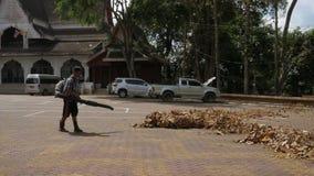 Человек с машиной воздуходувки лист очищает вверх листья осени на улице HD slowmotion Таиланд сток-видео