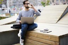 Человек с мобильным телефоном редактируя текст для рекламировать используя портативный компьютер соединился к радиотелеграфу 5G Стоковая Фотография RF