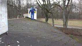 Человек с мхом брызга респиратора при химикаты растя на крыше дома видеоматериал