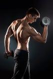 Человек с нагим торсом и гантели на черной предпосылке Стоковое Изображение RF