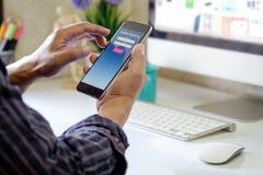 Человек с онлайн телефоном применения банка на месте для работы стола в офисе Стоковое Фото