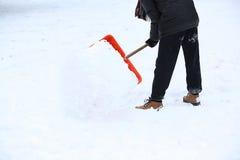 Человек с лопаткоулавливателем снега очищает тротуары Стоковые Фотографии RF