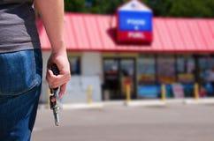 Человек с оружием готовым для того чтобы разбойничать ночной магазин Стоковая Фотография