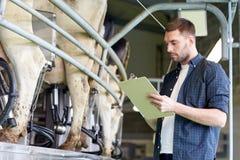 Человек с доской сзажимом для бумаги и доя коровами на молочной ферме Стоковая Фотография