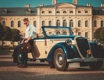 Человек с портфелем около классического автомобиля с откидным верхом стоковые изображения rf