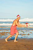 Человек с подарком на пляже Стоковое Изображение RF