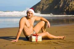 Человек с подарком рождества на пляже Стоковое Изображение
