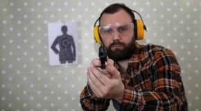 Человек с положенными дальше защитными изумлёнными взглядами и тренировка уха в пистолете sh Стоковые Изображения