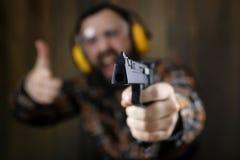Человек с положенными дальше защитными изумлёнными взглядами и тренировка уха в пистолете sh Стоковое Фото