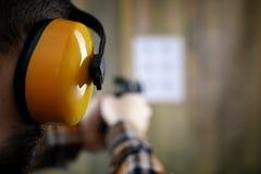 Человек с положенными дальше защитными изумлёнными взглядами и тренировка уха в пистолете sh Стоковые Фотографии RF