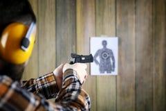 Человек с положенными дальше защитными изумлёнными взглядами и тренировка уха в пистолете sh Стоковые Фото