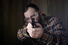 Человек с положенными дальше защитными изумлёнными взглядами и тренировка уха в пистолете sh Стоковые Изображения RF