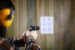Человек с положенными дальше защитными изумлёнными взглядами и тренировка уха в пистолете sh Стоковое фото RF